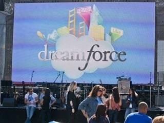 People gathered in front of a screen with the Dreamforce logo on it.