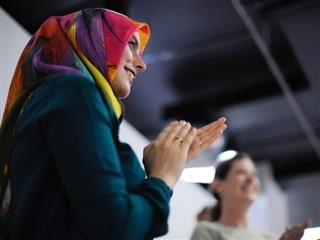 two female colleagues standing and applauding