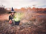 a little girl, dressed as a witch, making a spell in a caldron in the middle of a field