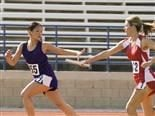 one woman passing the baton to her teammate in a relay race