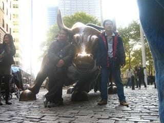 People leaning on the Wall Street bull.