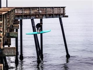 surfer jumping from a pier on his surf board caught in mid-air