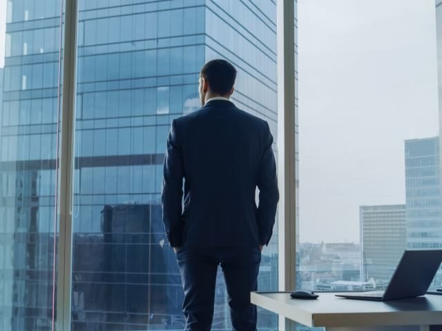 A businessman wearing a suit standing, hands in pockets, stands in his office, and contemplating technology purchases