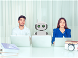 Young man and woman corporate employees with laptops sitting at table with robot colleagu