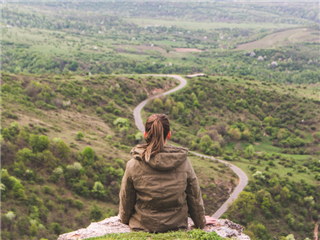 A woman sitting on a clifftop looking across the vista at a winding path and considering the future - customer journey concept