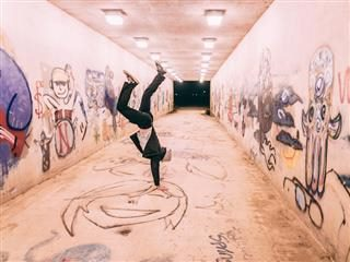 person doing handstand in hallway covered in grafitti