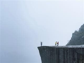 people standing at the edge of a cliff