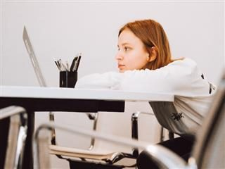 bored woman watching something on her laptop