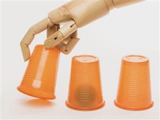 automaton hand playing variation of three card monte with cups