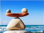 Rocks balancing atop one another, with the ocean in the background - technology vs upskilling concept