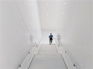 man looking around the corner at the top of a stairwell