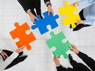 Marketing and IT professionals holding interlocking jigsaw pieces, working together