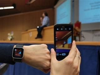 A left hand with a wearable watch and a right hand holding a smartphone.