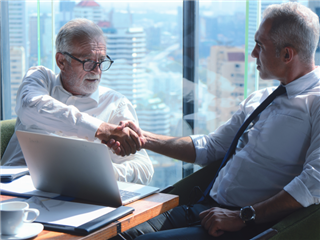 Two businessmen in an office high-rise sharing a handshake, behind them a large window shows a cityscape.  - Customer acquisition concept