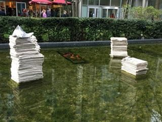 Three stacks of newspapers in water.