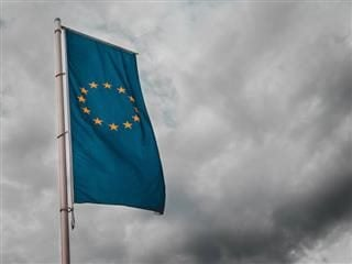 EU flag against a grey, overcast sky