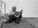 A man sits on steps and reads a newspaper.