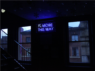 A city street with a neon sign 'more this way' - greater than concept