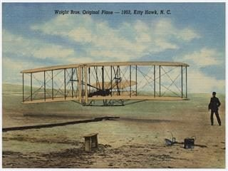 View of a wooden airplane hovering above the ground, while a man at the left watches  on.