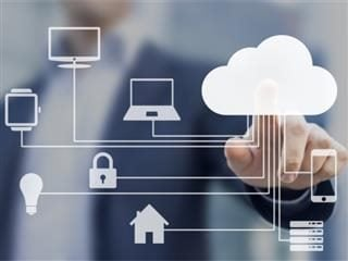 Businessman touching a cloud connected to many internet of thing devices on a virtual screen. IOT concept