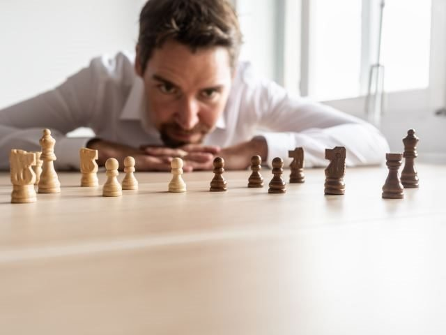 A businessman looking at black and white chess pieces on office desk - strategic thinking concept