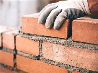 A  close up of industrial bricklayer installing bricks on a construction site - Brick and mortar stores concept