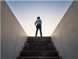 A businessman standing at the top of the stairwell in the sunshine - scaling up strategy concept