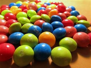 Different-colored Skittles on a table.