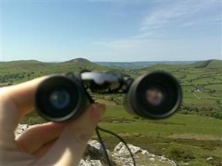 someone holding up a pair of binoculars overlooking green fields.