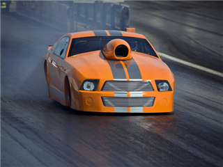 An orange supercharged dragster racing down the track at top speed - DAM concept