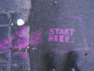 """start here"" spray painted in purple paint on the sidewalk. someone's sneakers visible in shot"