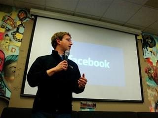 Facebook CEO Mark Zuckerberg holding a microphone giving a talk.