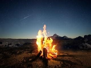 A wood-log fire with a mountain backdrop