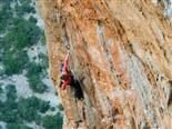 woman climbing  up the face of a steep rock in Greece