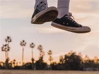 person's sneaker-clad feet caught mid-jump, palm trees and beach scene in background