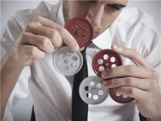 A businessman working with gears - building concept