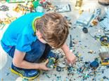 boy standing in the midst of electronic parts, building something