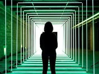 woman standing in a hall lit by surrounding neon lights