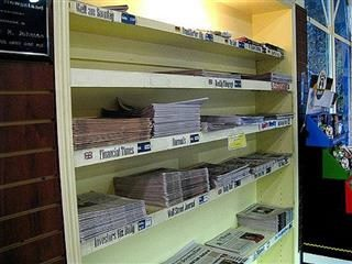 newspapers on shelves on a wall.