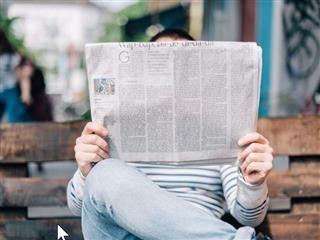 Un homme lisant un journal sur un banc de parc extérieur - News bytes