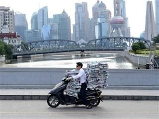 man driving a motorcycle carrying two large stacks of newspapers.