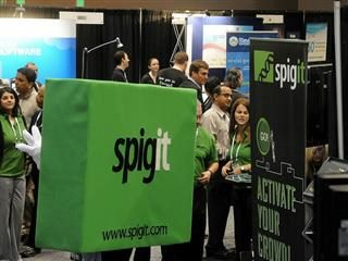 people at spigit exhibition booth at tech conference