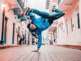 man balancing on one hand in middle of breakdancing move