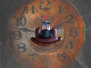 person sitting in middle of clock image painted on floor