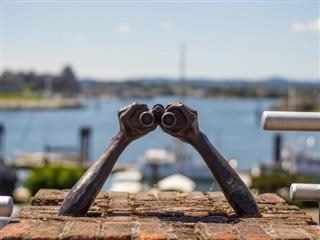 sculpture of arms holding binoculars facing a harbor