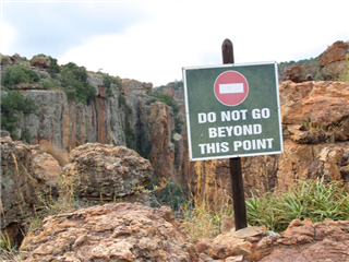 A sign post warning not to go beyond this point or fall over the cliff - beyond digital transformation concept