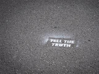 "graffiti on sidewalk that reads: ""Tell the truth"""