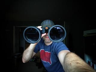 man with REALLY big binoculars in front of his face