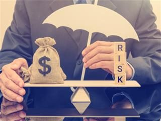 Marketing fraud: Businessman holds a white umbrella, protects a dollar bag on basic balance scale, defends money from being cheat or fraud