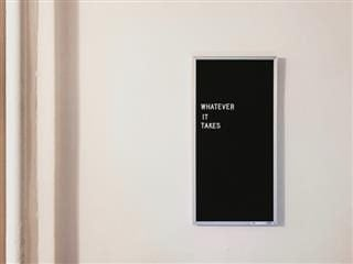 "a sign hanging on a cream-colored wall which states ""Whatever it Takes"""